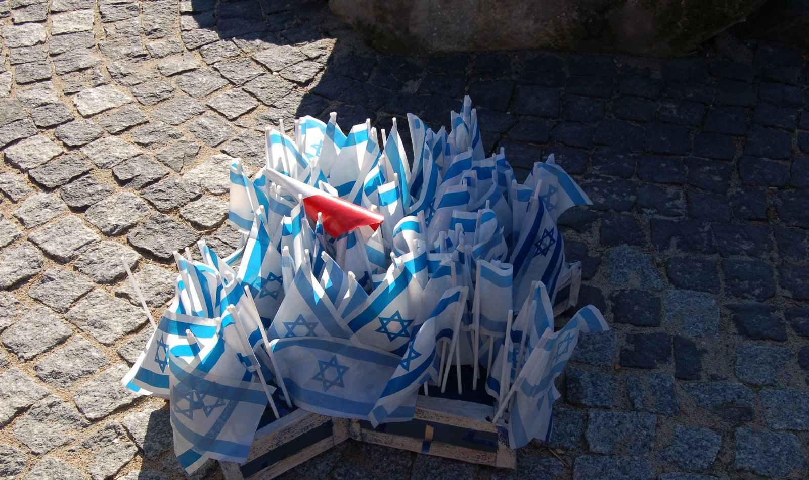 Liczne proporce - flagi Izraela i flaga Polski pośród nich - całość  na drewnianym świeczniku w kształcie gwiazdy Dawida